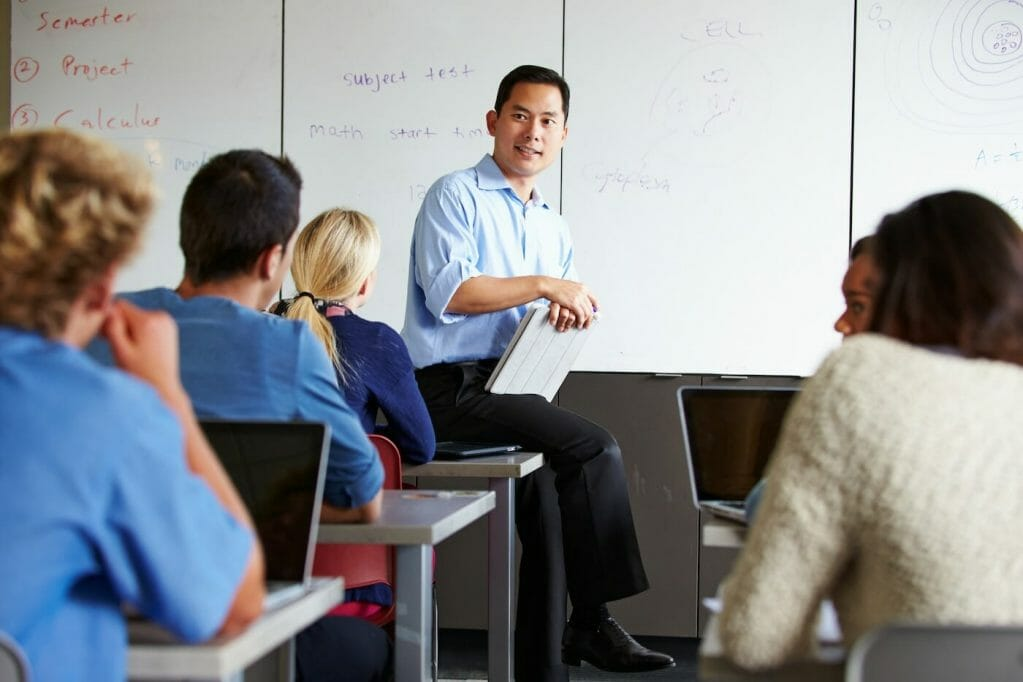 Instructor with students in class using laptops