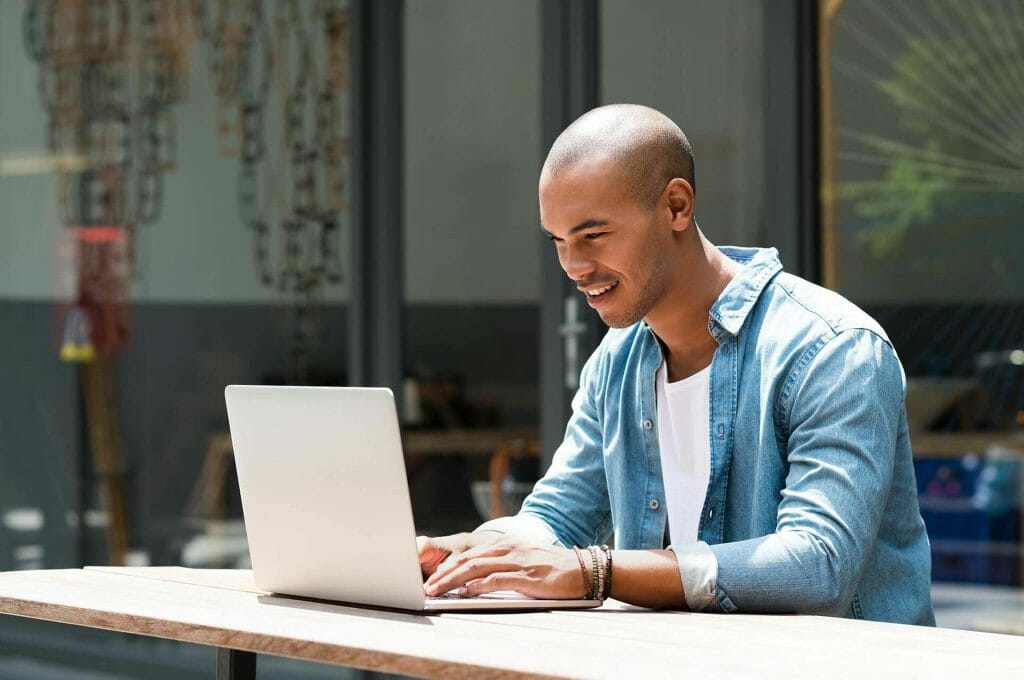 Male student on laptop taking proctored exam